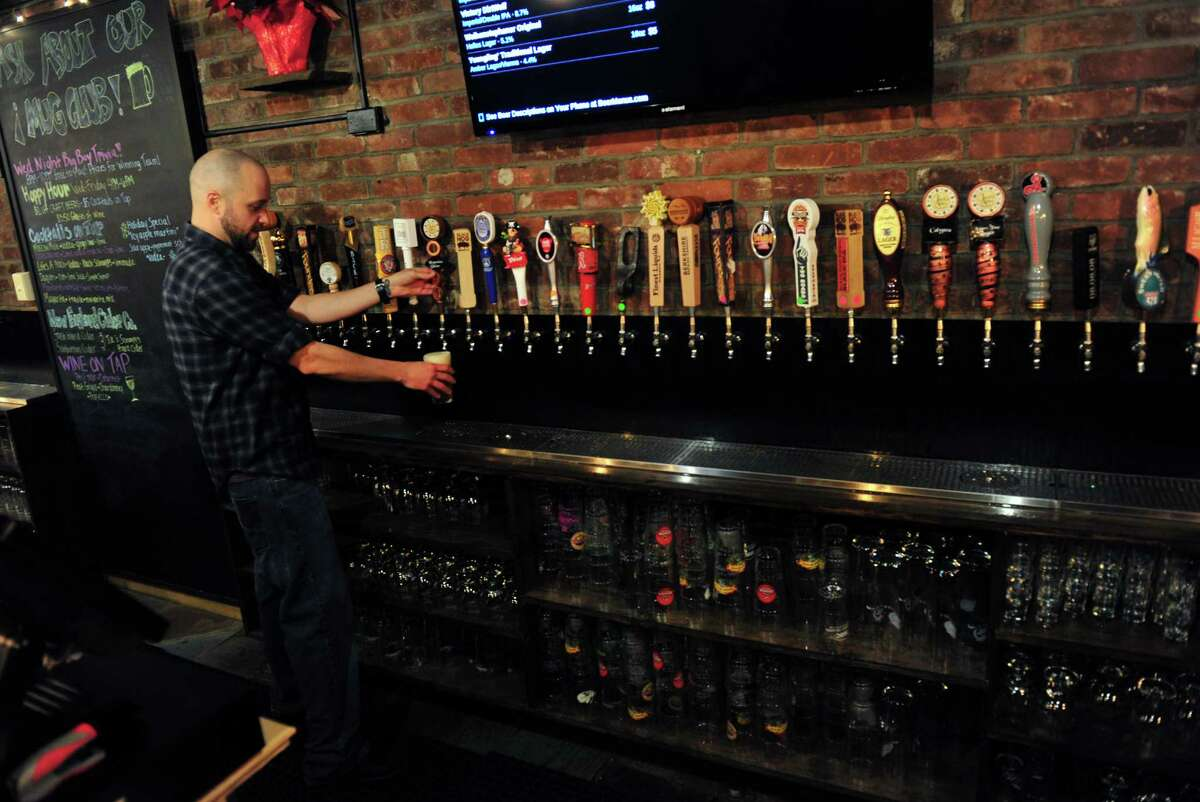 T.H.C. (The Hops Company) bartender Christopher Cardia fills a drink order at the new business in Derby, Conn. on Wednesday Dec. 16, 2015. Opened for a few weeks now, T.H.C. is located in what was formerly the Grassy Hill Lodge. Zupardi's Apizza, out of West Haven, and Ricky D's Rib Shack, out of New Haven, are set up at T.H.C. to provide the food to patrons.