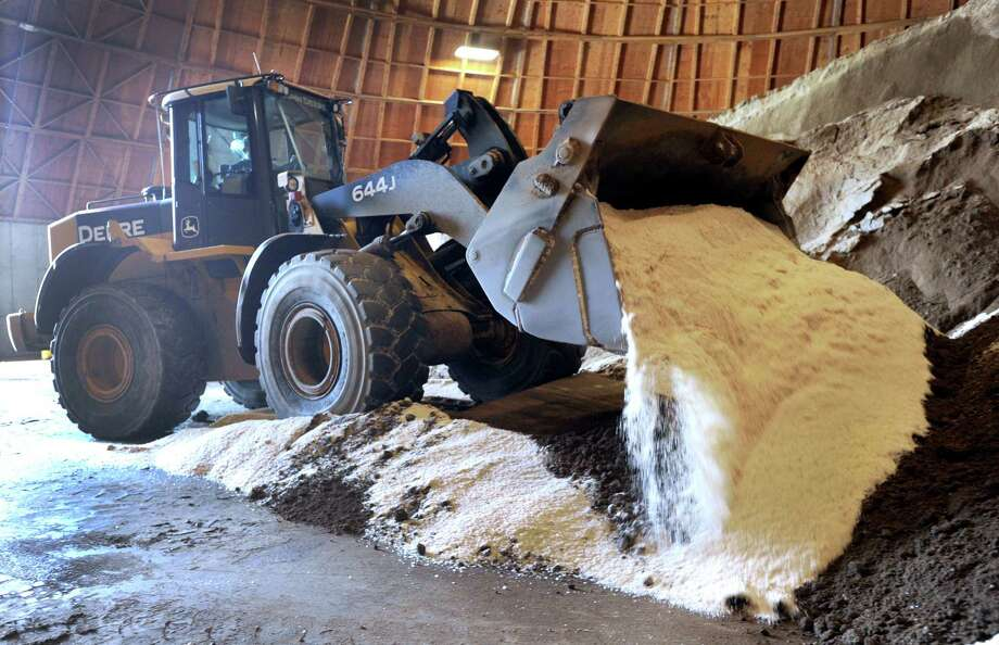 A Danbury Highway Department worker mixes salt and sand in preparation for a winter storm last year. The city is now planning to use a straight salt material to treat slick roadways. Photo: Carol Kaliff / Hearst Connecticut Media / The News-Times