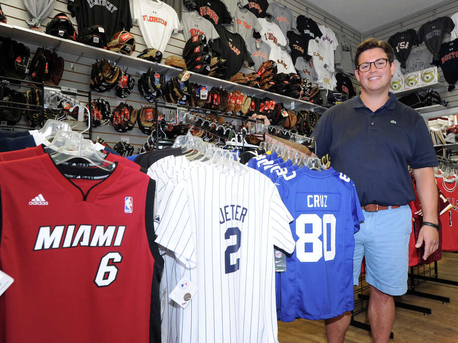 Bruce Park Sports owner, Mark Bisanzo, displays his store's popular selling jerseys, that include the No. 6 Miami Heat jersey of LeBron James, Derek Jeter's Yankee jersey and the jersey of Victor Cruz, a N.Y. Giant wide receiver, in the Greenwich store, Conn., Tuesday, June 10, 2014. Bruce Park Sports celebrated 45 years in business this month. Photo: Bob Luckey / Bob Luckey / Greenwich Time