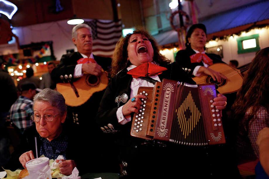 Eva Ybarra, center, sings with Ricardo Urbano and Maria Ruiz at Chris Madrid's as Nora Catlett, 88, left, dines with her family in San Antonio on Friday, Dec. 18, 2015. Photo: Lisa Krantz /SAN ANTONIO EXPRESS-NEWS / SAN ANTONIO EXPRESS-NEWS