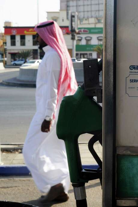 A Saudi man walks past a pump at a petrol station Monday in the Red Sea city of Jeddah. A royal decree announced that petrol prices would go up by 50 percent effective Tuesday. Even with that jump, Saudis will pay less than a dollar per gallon. Photo: Amer Hilabi /AFP / Getty Images / AFP
