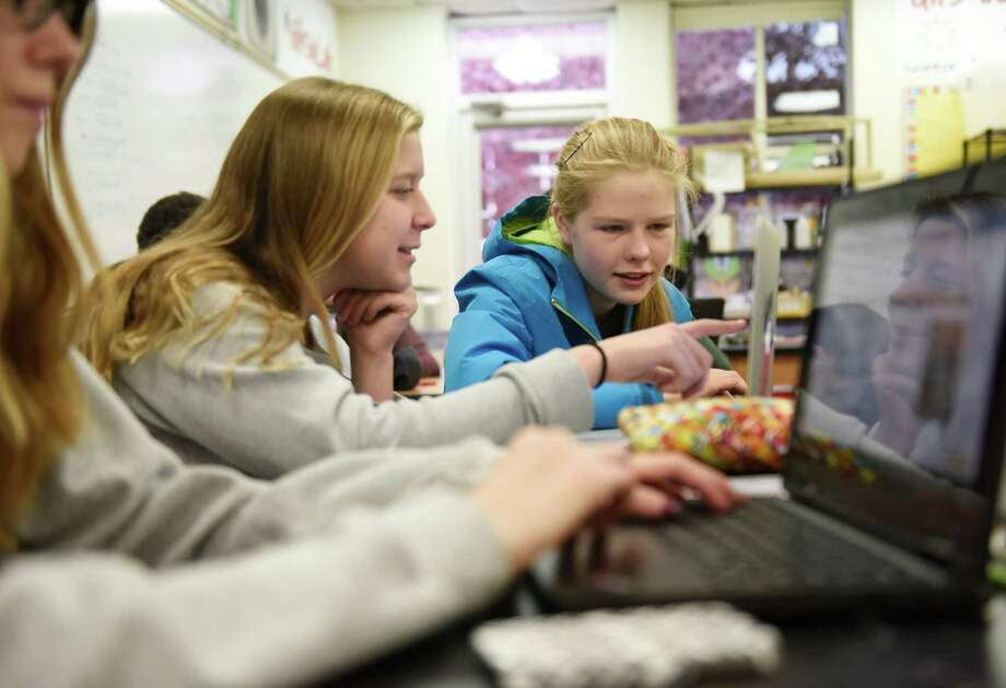 (Above) Sophomores Nicole Wood, left, and Flora Braes work on a project, and STEM teacher Brian Walach helps sophomore Chloe Boucher (below) with a project using laptops in the Innovation Lab. Photo: Tyler Sizemore / Hearst Connecticut Media / Greenwich Time