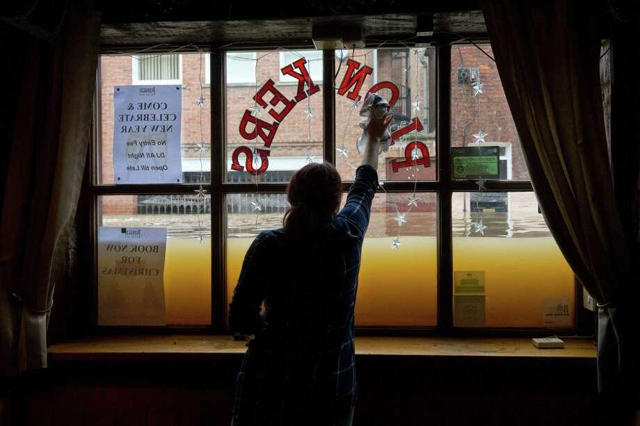 A woman cleans the window inside her wine bar Monday as floodwaters rise from the rivers Foss and Ouse, after they burst their banks in York, England. Photo: JUSTIN TALLIS, Stringer / AFP