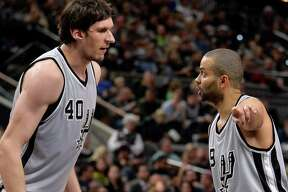 San Antonio Spurs guard Tony Parker, right, of France, talks to Spurs center Boban Marjanovic, of Serbia, during the second half of an NBA basketball game against the Denver Nuggets, Saturday, Dec. 26, 2015, in San Antonio. (AP Photo/Darren Abate)