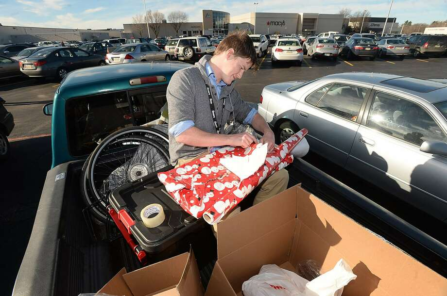 On Christmas Eve, Mike Harvey of Edinboro, Pa., was wrapping presents in his pickup truck outside a shopping mall in Millcreek Township.  Photo: Jack Hanrahan, MBI / ERIE TIMES-NEWS