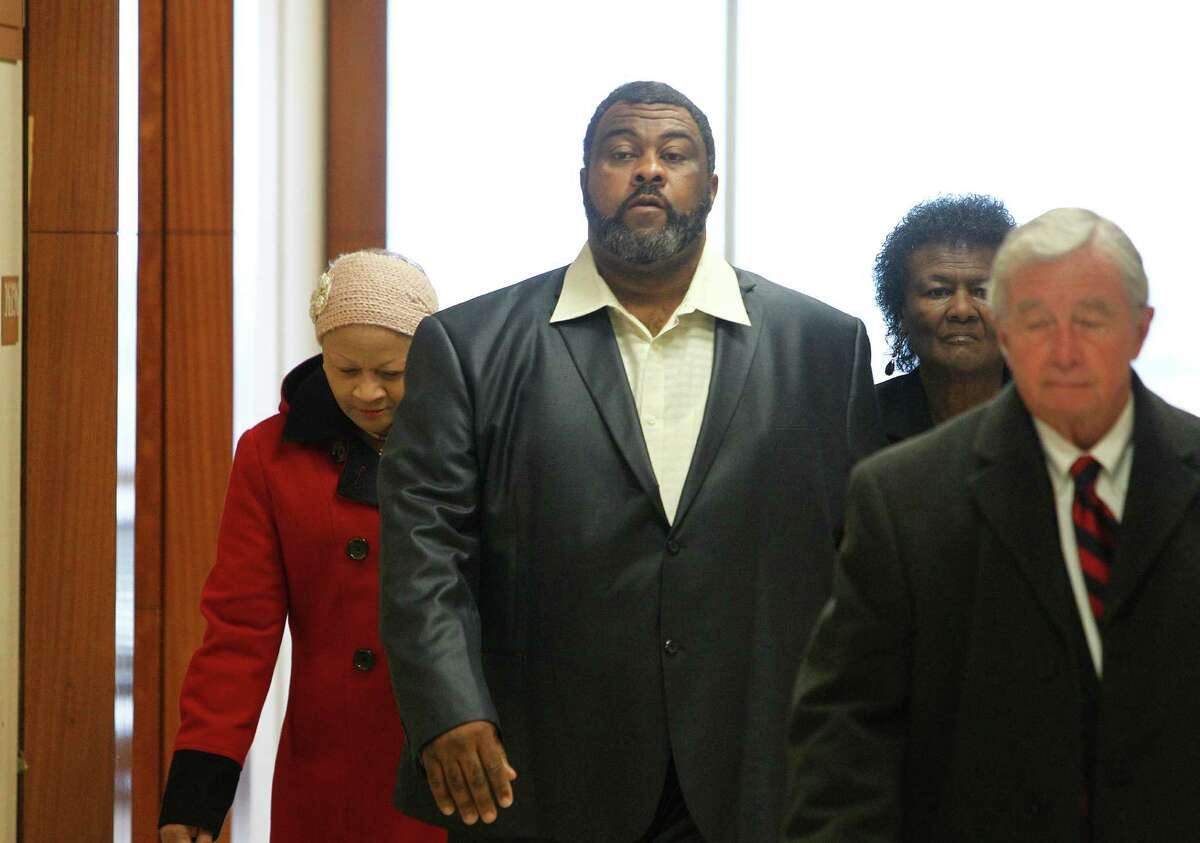 Tyrone Auzenne, center, leaves court Monday with his attorney Dick DeGuerin. The former city of Houston worker is accused of fatally shooting his supervisor.