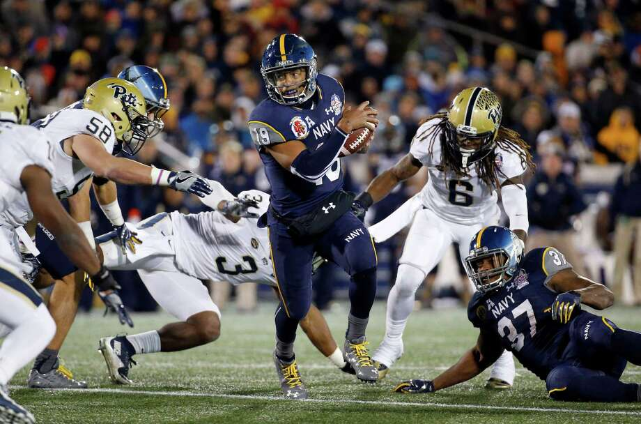 Navy quarterback Keenan Reynolds, center, carries the ball in the second half. Reynolds finished with 144 rushing yards on 24 carries, adding his 88th TD. Photo: Patrick Semansky, STF / AP