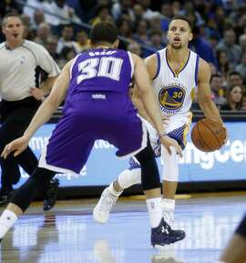 Golden State Warriors' Stephen Curry drives on Sacramento Kings' Seth Curry in 2nd quarter during NBA game at Oracle Arena in Oakland, Calif., on Monday, December 28, 2015.