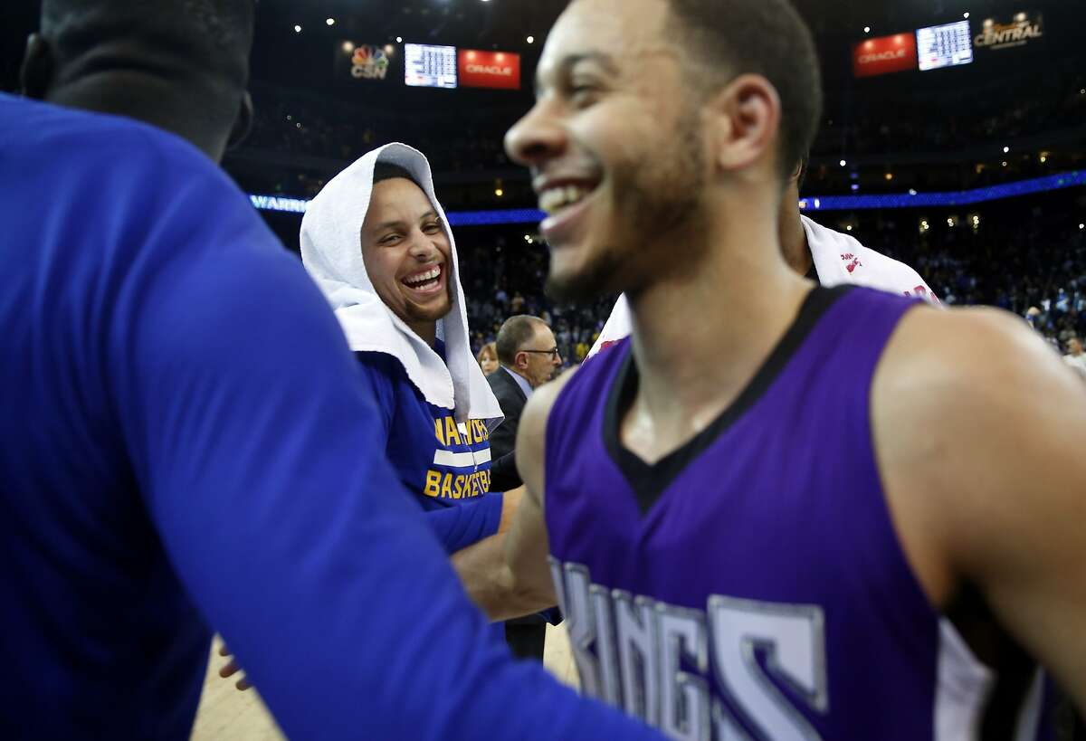 Golden State Warriors' Stephen Curry and his brother Sacramento Kings' Seth Curry greet each other after Warriors' 122-103 win during NBA game at Oracle Arena in Oakland, Calif., on Monday, December 28, 2015.