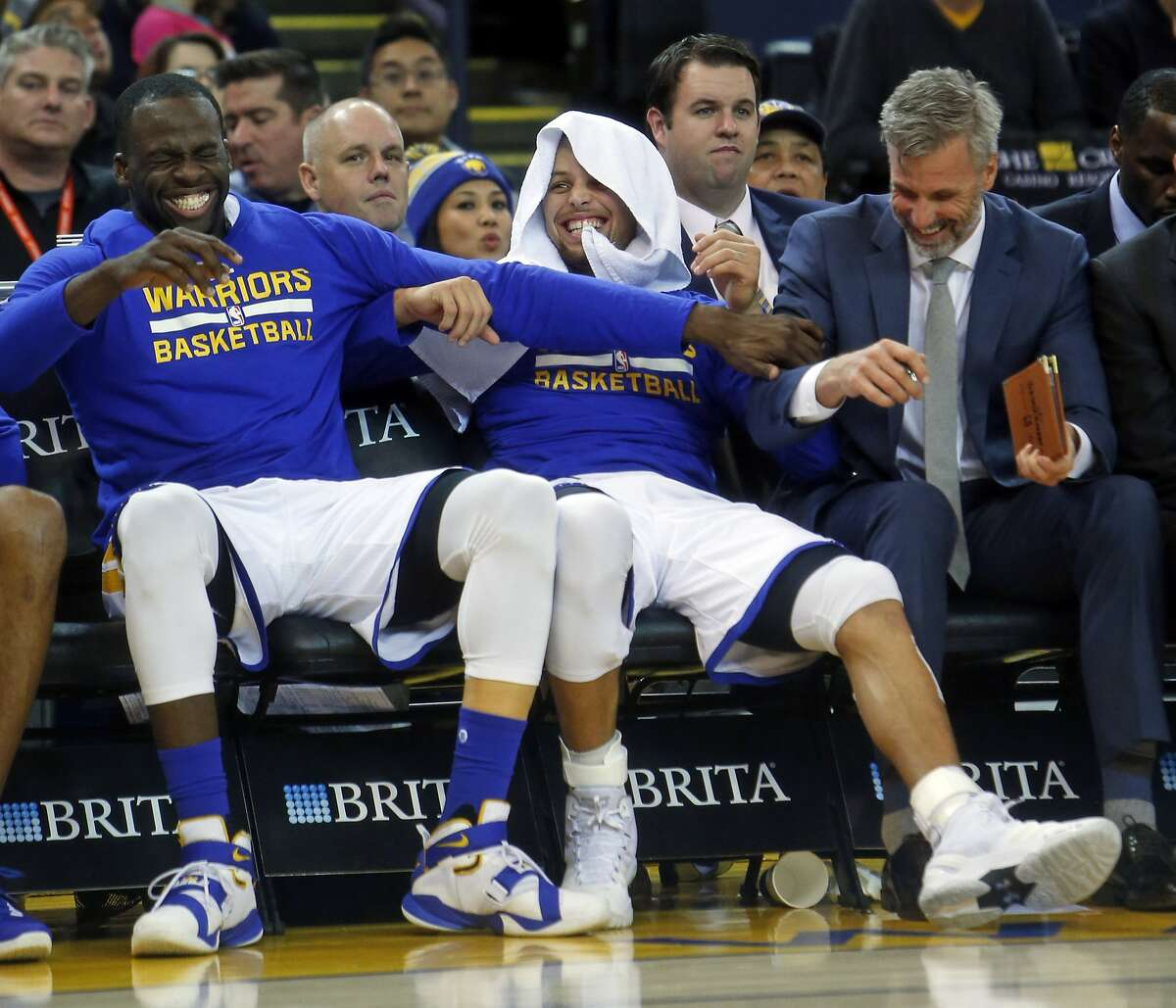Golden State Warriors' Draymond Green, Stephen Curry and assistant coach Bruce Fraser enjoy 4th quarter of Warriors' 122-103 win over Sacramento Kings during NBA game at Oracle Arena in Oakland, Calif., on Monday, December 28, 2015.