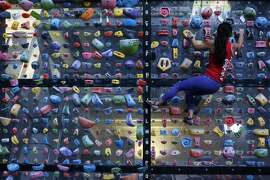 Stephanie Pound, Sr Director of Bay Area & Marketing at Planet Granite, demonstrates her climbing technique on the system board at the San Francisco location in the Presidio on Monday, Dec 28, 2015.