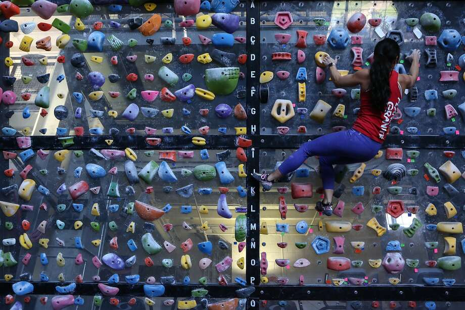 Stephanie Pound, Sr Director of Bay Area & Marketing at Planet Granite, demonstrates her climbing technique on the system board at the San Francisco location in the Presidio on Monday, Dec 28, 2015. Photo: Amy Osborne, Special To The Chronicle