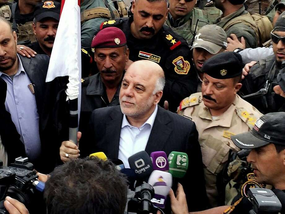 Prime Minister Haider al-Abadi raises an Iraqi flag in Ramadi after it was partly retaken by the military. Photo: Uncredited, Associated Press