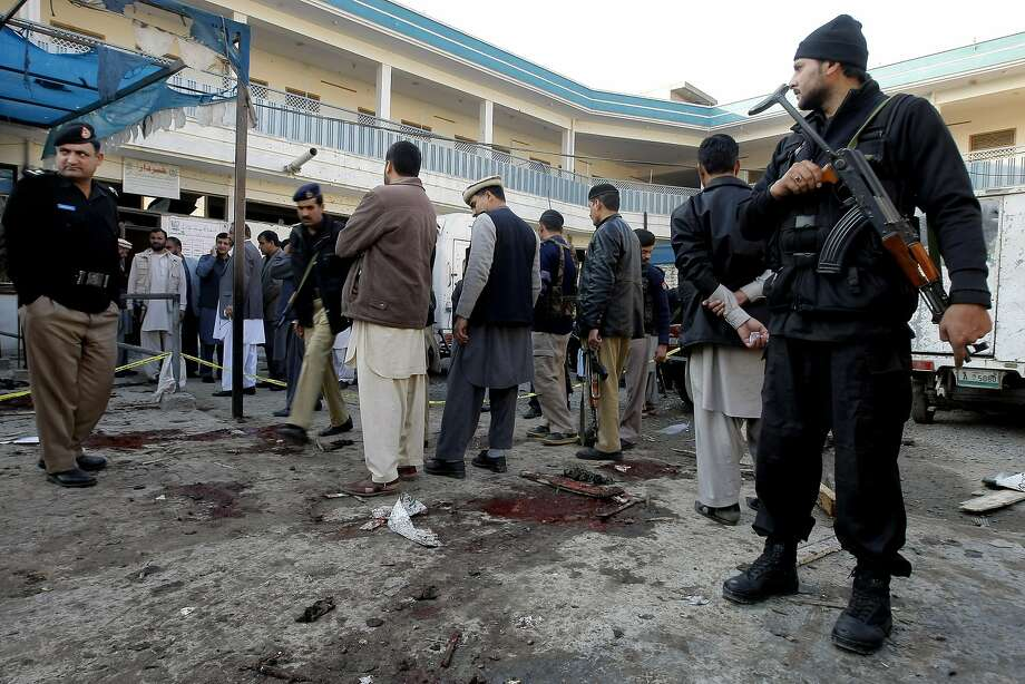 Pakistani security officials examine the site of a suicide attack in the northwestern city of Mardan. Photo: Mohammad Sajjad, Associated Press