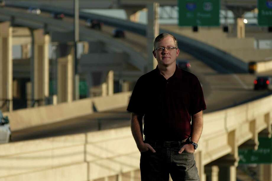 Brian Purcell, who started a website called the Texas Highwayman, keeps tabs on transportation of all kinds in San Antonio and the state. He stands at the Interstate 10 and Loop 410 interchange in San Antonio on Dec. 22. Photo: Billy Calzada /San Antonio Express-News / San Antonio Express-News