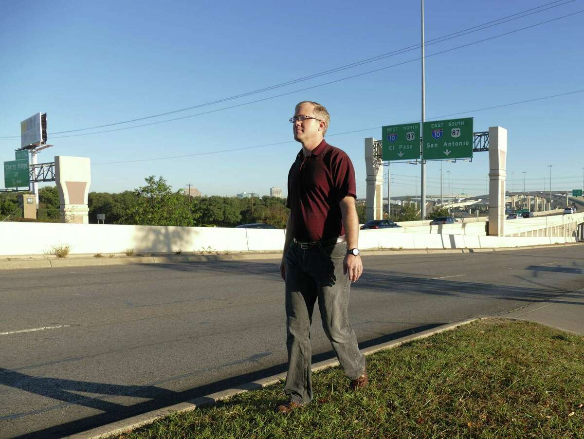 Brian Purcell is an information technology manager by day but has a keen interest in transportation. He walks at the Interstate 10 and Loop 410 interchange in San Antonio on Dec. 22.