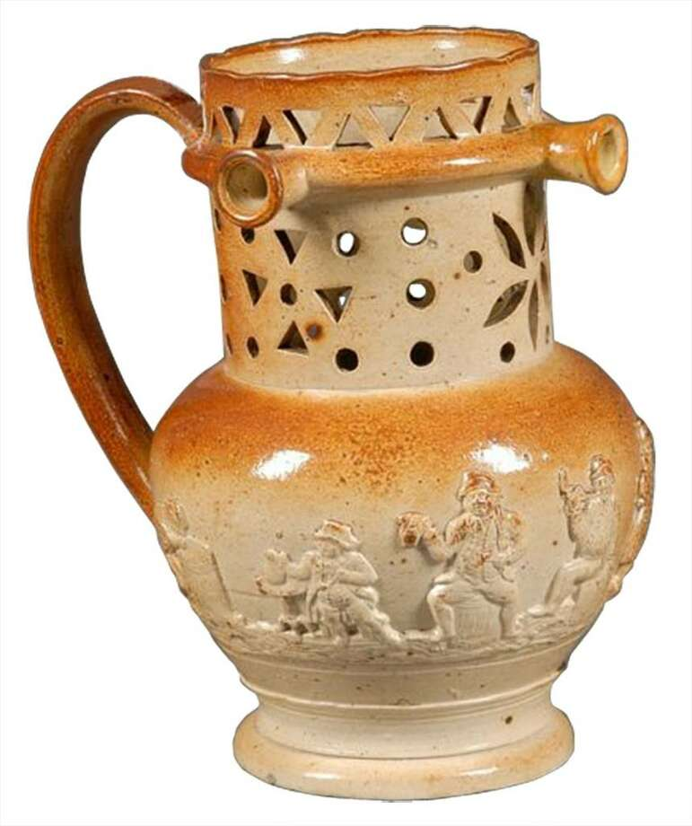 Try drinking from this pierced puzzle jug without getting wet (use the handle as a straw). This 19th-century stoneware jug sold for $356 at a Skinner auction in Boston. Photo: Contributed Photo / The News-Times Contributed