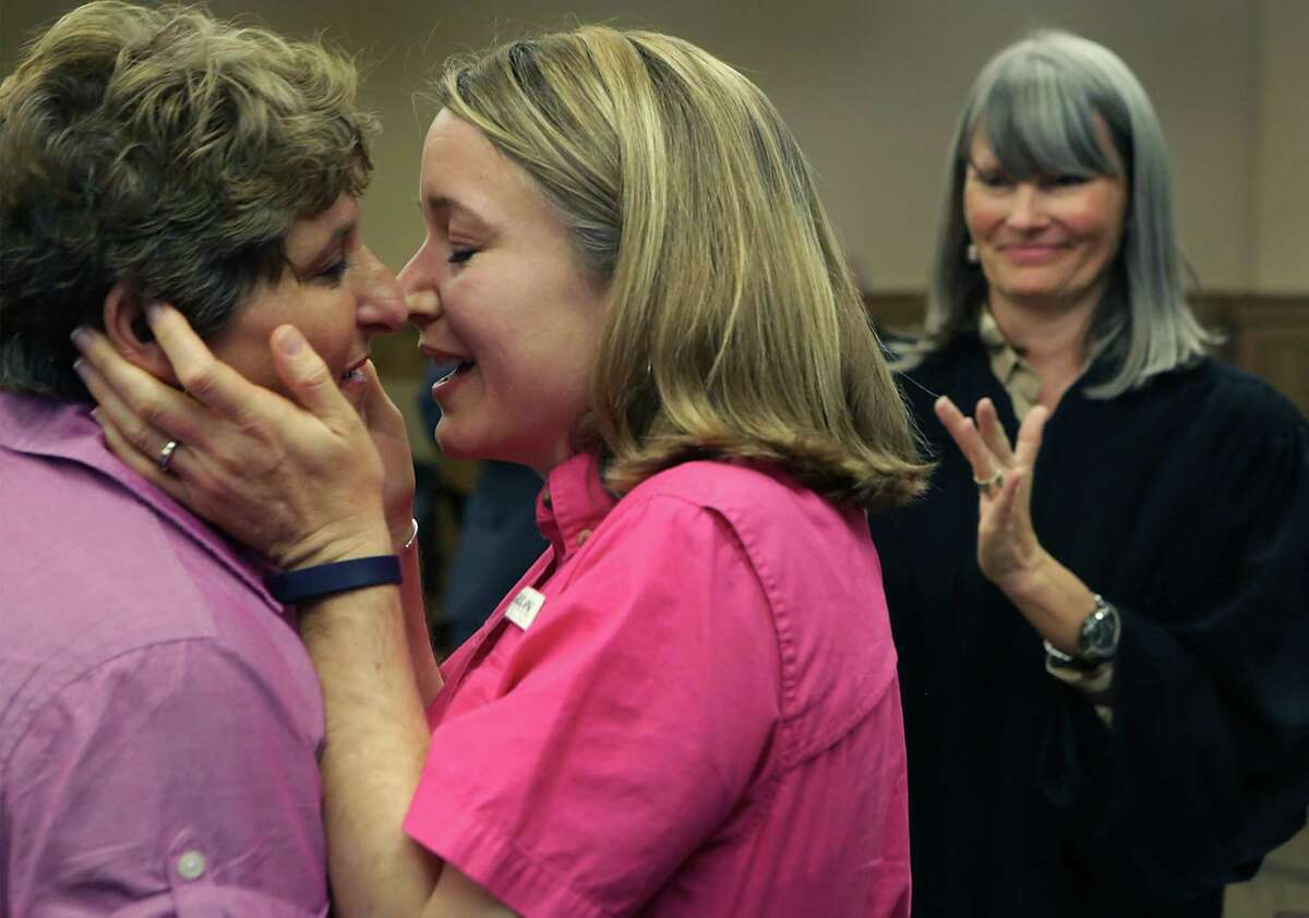 Celeste Branstetter, center, embraces her partner Felice Garcia's face for a kiss after they were married by Judge Karen Pozza at the Bexar County Courthouse. Gay couples were able to get their marriage license at the Bexar County Courthouse after the Supreme Court voted in favor of same sex weddings, on Friday, June 26, 2015. Some of the couple were married in the Presiding Court the same day.