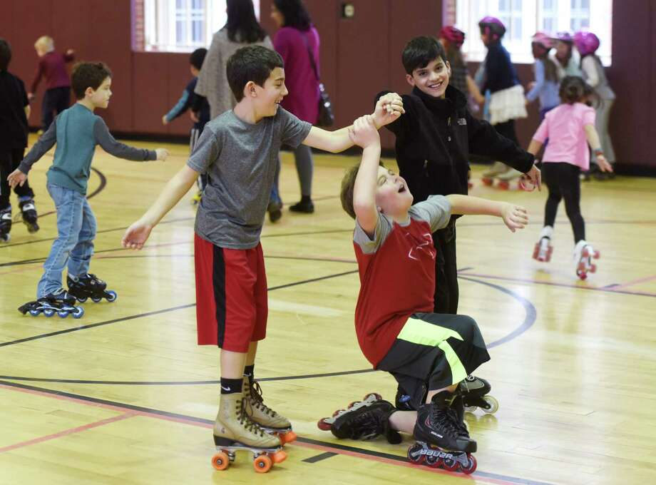 Brayden Magliulo, center, 10, of Glenville, takes a spill while skating with fellow Glenville kids John Sarubbi, left, 10, and Carter Bagaria, 10, at the Greenwich Parks & Recreation Roller Skating Party at Bendheim Western Greenwich Civic Center in the Glenville section of Greenwich, Conn. Tuesday, Dec. 29, 2015.  About 40 kindergarten through sixth-grade kids and parents skated and played games like limbo and elimination.  The annual event sponsored by the Parks & Rec. Department gave the children an active and fun activity to do during winter break when school is closed. Photo: Tyler Sizemore, Hearst Connecticut Media / Greenwich Time