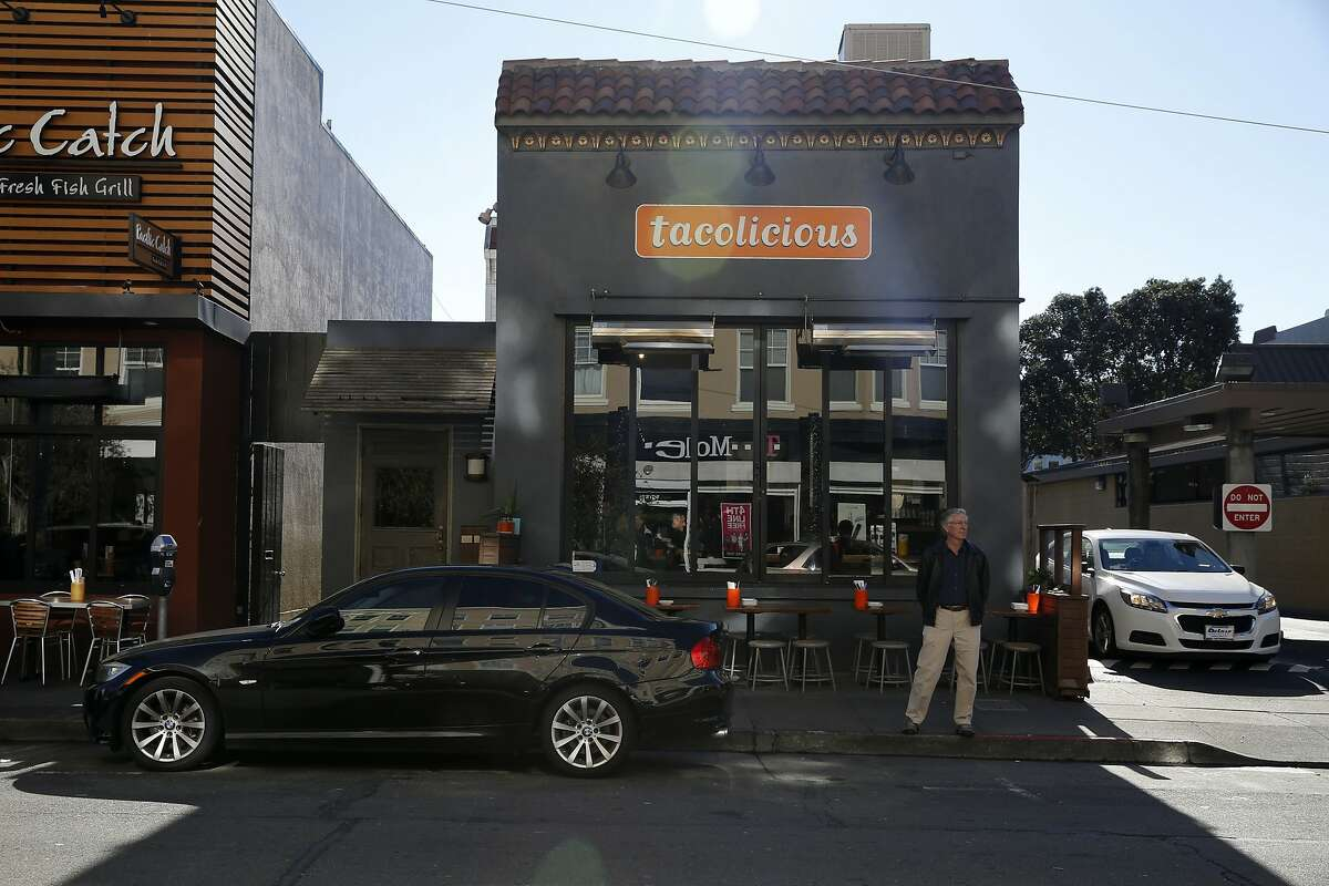 A man stands near a parked car outside Tacolicious on Chestnut Street in San Francisco, California, on Tuesday, Dec. 29, 2015.