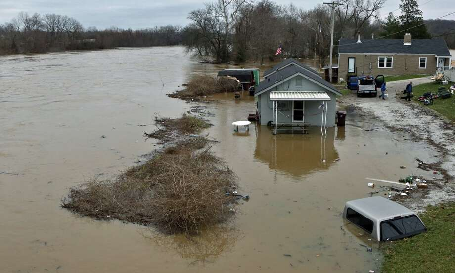 People move some of their belongings to higher ground on Tuesday, Dec. 29, 2015, as the Meramec River continues to rise next to the Gravois Road bridge in old town Fenton, Mo. Torrential rains over the past several days pushed already swollen rivers and streams to virtually unheard-of heights in parts of Missouri and Illinois. Record flooding was projected at some Mississippi River towns, and the Meramec River near St. Louis was expected to get to more than 3 feet above the previous record by late this week   Photo: J.B. Forbes, Associated Press / St. Louis Post-Dispatch