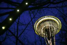 Christmas lights and the Space Needle light up the evening sky near Seattle Center, Monday, Dec. 28, 2015.