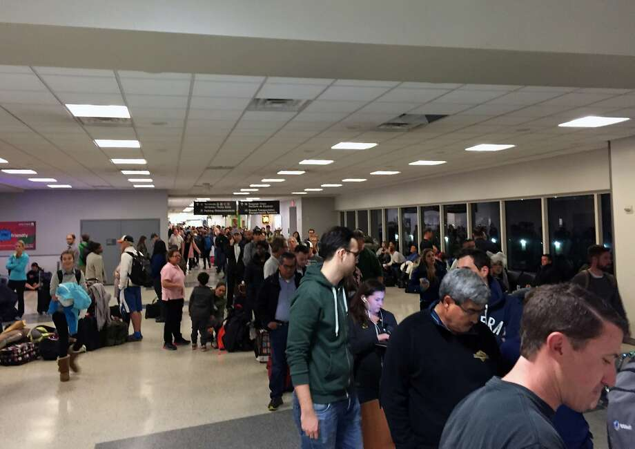 Stranded travelers line up for customer assistance at the Houston airport's United terminal early Monday.