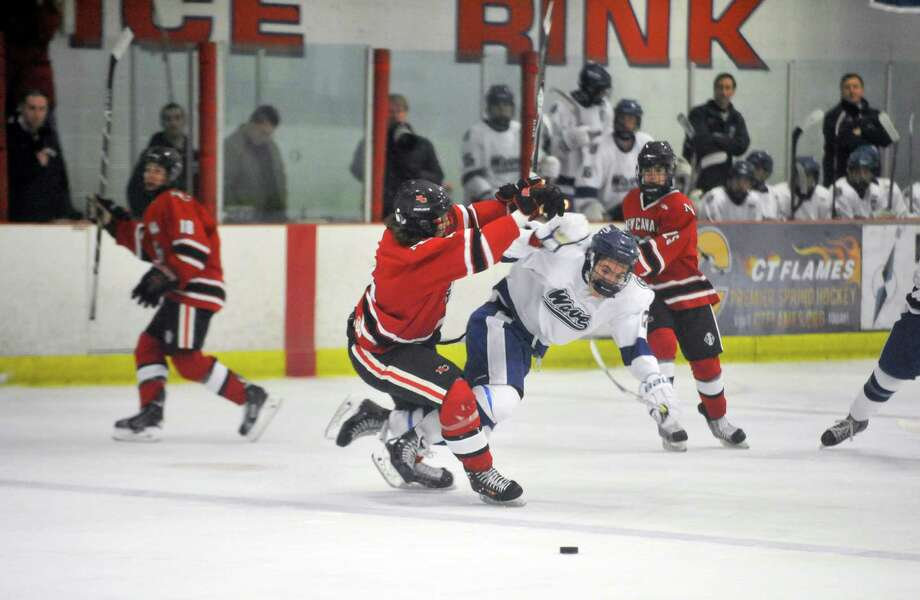 New Canaan defender Teddy Hood, left, checks Darien's Edward Glassmeyer during a game at Darien Ice Rink on Dec. 29, 2015. Photo: Michael Cummo / Hearst Connecticut Media / Stamford Advocate