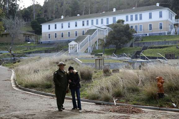 Interpreter Ben Fenkell (left) and Angel Island Immigration Station Foundation Director of Programs Lisa Van Cleef laugh together in front of part of the former immigration center on Angel Island State Park, California, on Monday, Dec. 28, 2015.