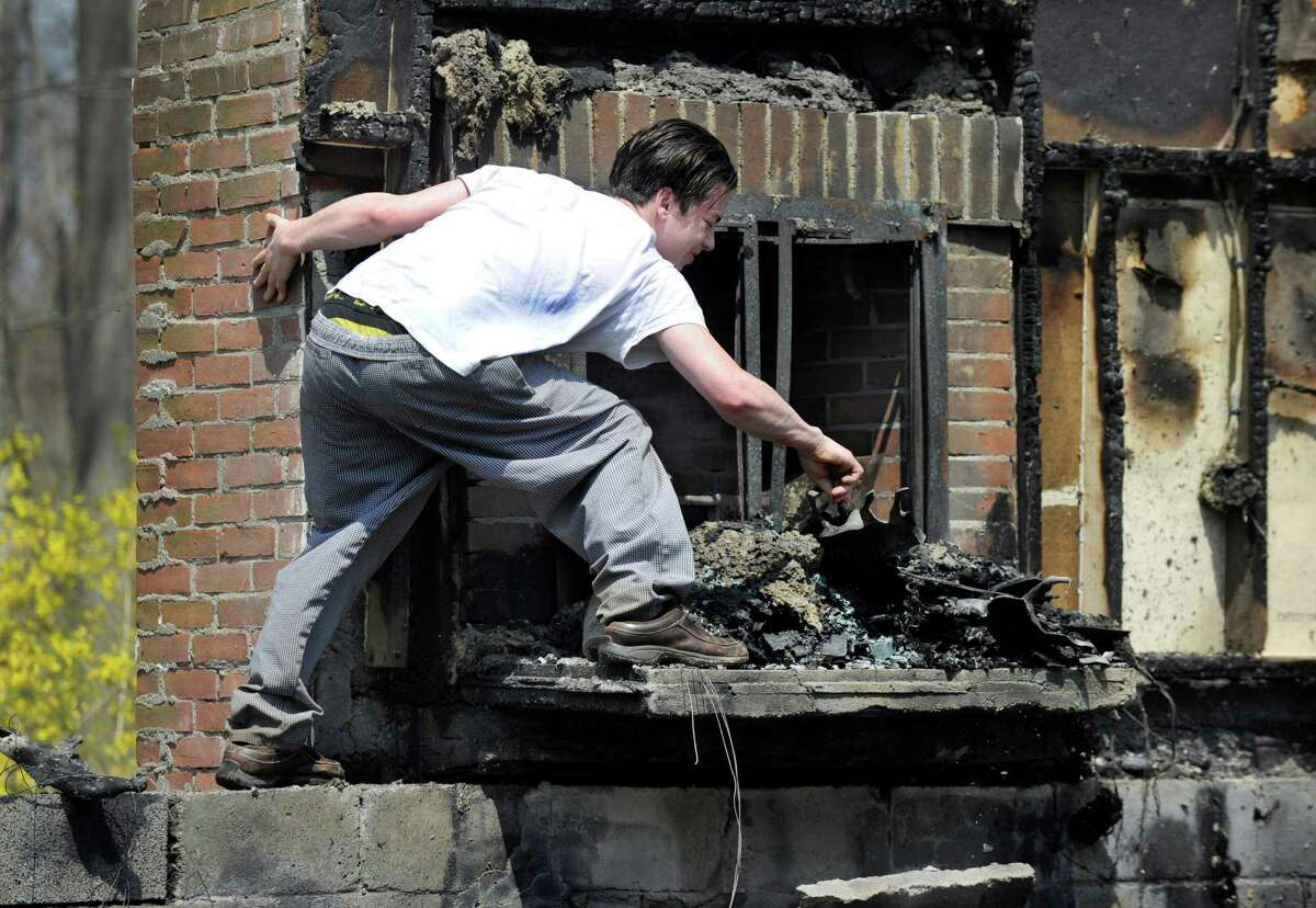 CJ Donahue, walks through the rubble that is left after an early morning fire destroyed the house, owned by his family, on 4 Aunt Park Lane in Newtown, Conn., where CJ lived with two others, Monday, May 4, 2015.