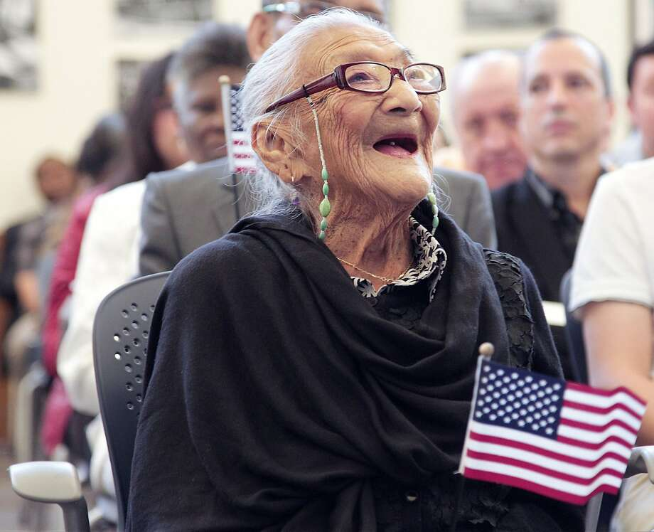 Citizen candidate Juana Hernandez, 101, smiles as she looks upward at a video presentation during her swearing-in ceremony for U.S. citizenship on Dec. 29, 2015 in Miami.  About 141 citizenship candidates originating from 37 countries were sworn in as the last group of new U.S. citizens for 2015 inside USCIS Miami Field Office on Tuesday. Photo: Carl Juste, McClatchy-Tribune News Service
