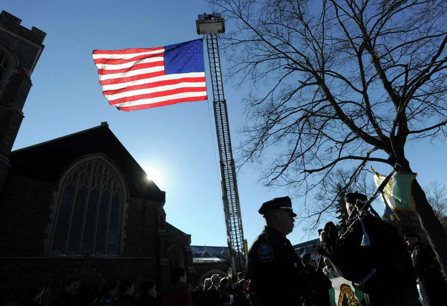 A giant American flag flew from a Greenwich fire truck as the bagpipes were played at the conclusion of the memorial serivce for Greenwich Selectman David Theis at Christ Church in Greenwich, Conn., Saturday, Jan. 10, 2015. Theis, a Greenwich native, passed away unexpectedly on December 23. Photo: Bob Luckey / Greenwich Time