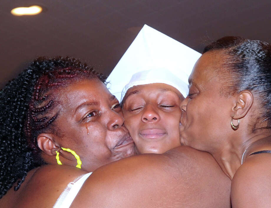 Stamford Academy graduate LaQuariah Corder, center, gets a kiss from her aunt, Mary Jordan, left, and her mother, Lavette McMillian, right, during the Stamford Academy Graduation at the Domus auditorium in Stamford, Conn., Wednesday, June 17, 2015. Photo: Bob Luckey, Staff Photographer / Greenwich Time