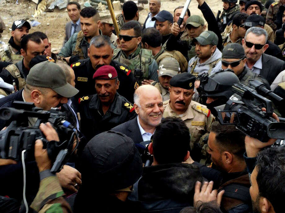 Iraqi Prime Minister Haider al-Abadi, center, smiles as he tours the city of Ramadi after it was retaken by the security forces in Ramadi, 70 miles (115 kilometers) west of Baghdad, Iraq, Tuesday, Dec. 29, 2015. Iraqi military forces on Monday retook a strategic government complex in the city of Ramadi from Islamic State militants who have occupied the city since May. (AP Photo) Photo: Uncredited, STR / AP