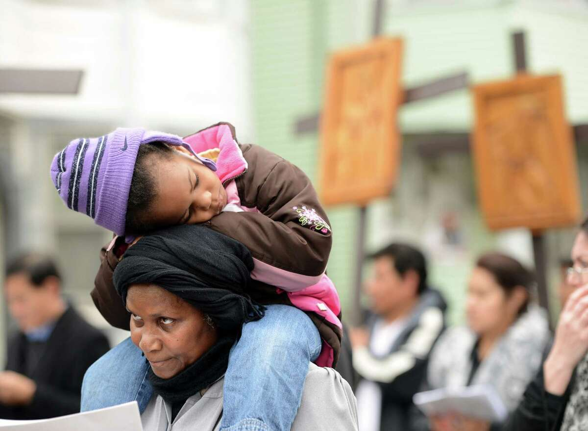 Maud Joseph, of Bridgeport, carries her 3-year-old granddaughter Kaminnya Alibey on her shoulders Friday, April 3, 2015, during the annual Good Friday procession which began at St. Augustine Cathedral on Washington St. and ended at St. Patrick Church on North Ave.