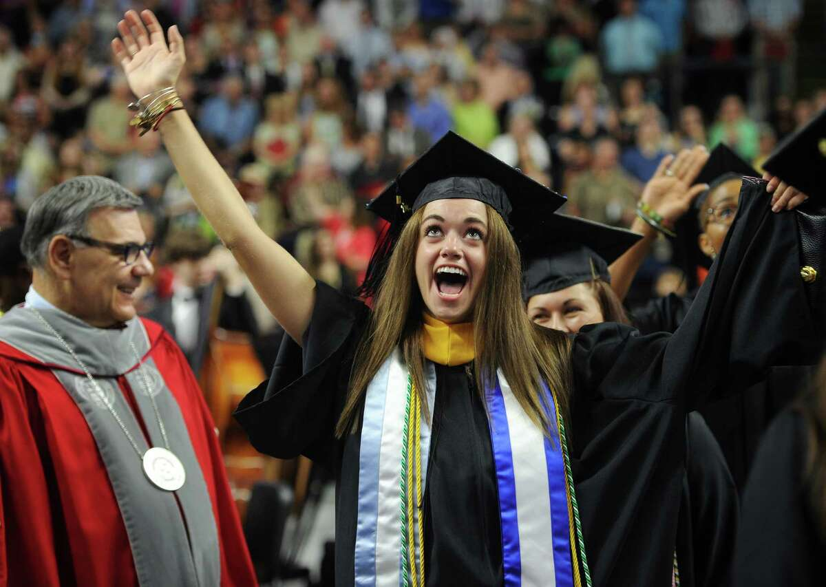 Graduate Meaghan McGann waves to the crowd during the procession to kick off the Sacred Heart University Graduation at the Webster Bank Arena in Bridgeport, Conn. on Sunday, May 17, 2015.