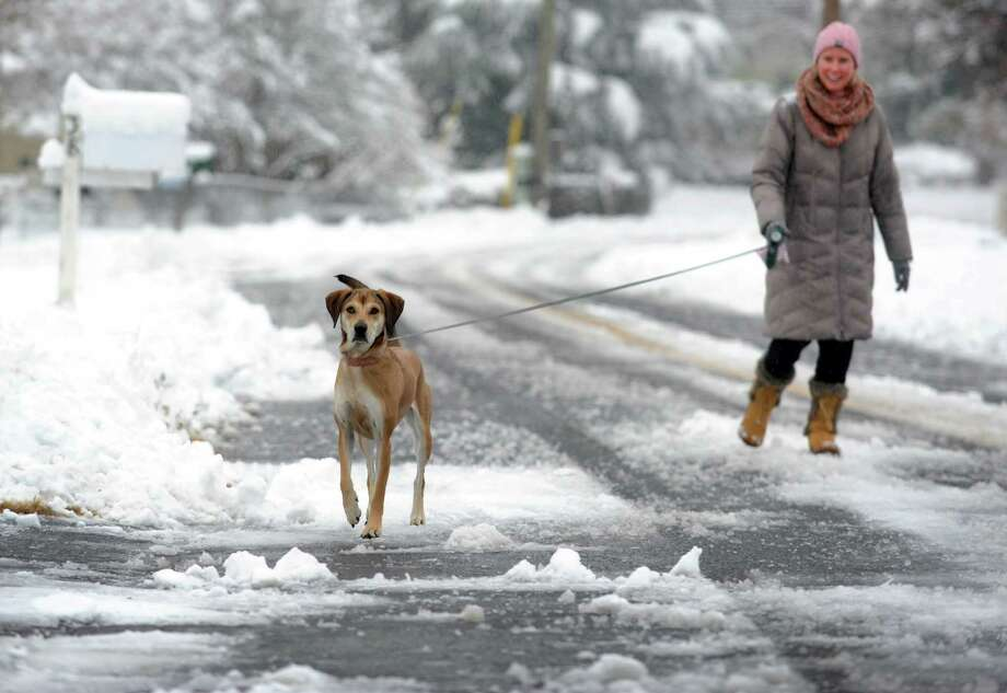 Kristen Hardiman walks her dog Barkley through the snow covered roads in Fairfield, Conn. on Saturday, Jan. 24, 2015. After an overnight accumulation, the snow transitioned to rain by late morning. Photo: Cathy Zuraw, Hearst Connecticut Media / Connecticut Post