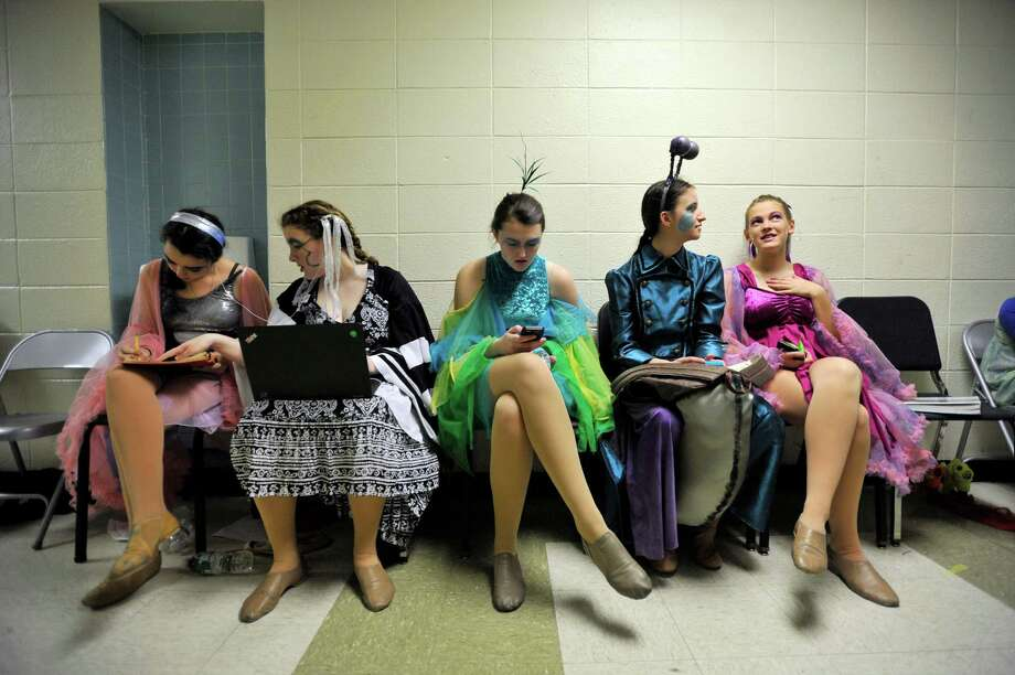 The cast of The Little Mermaid occupy themselves before showtime, with some opting to do homework and others opting to talk or text. Photo: Michael Cummo, Hearst Connecticut Media / Stamford Advocate