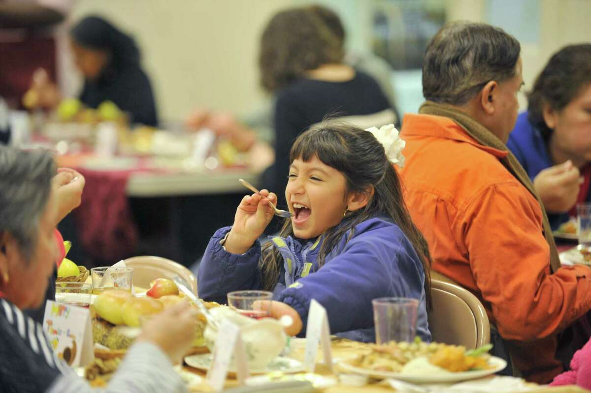 Camilla Useche, 6, sings into her spoon after finishing her Thanksgiving meal during the Congregational Church of Stamford's 44th annual free community Thanksgiving dinner.