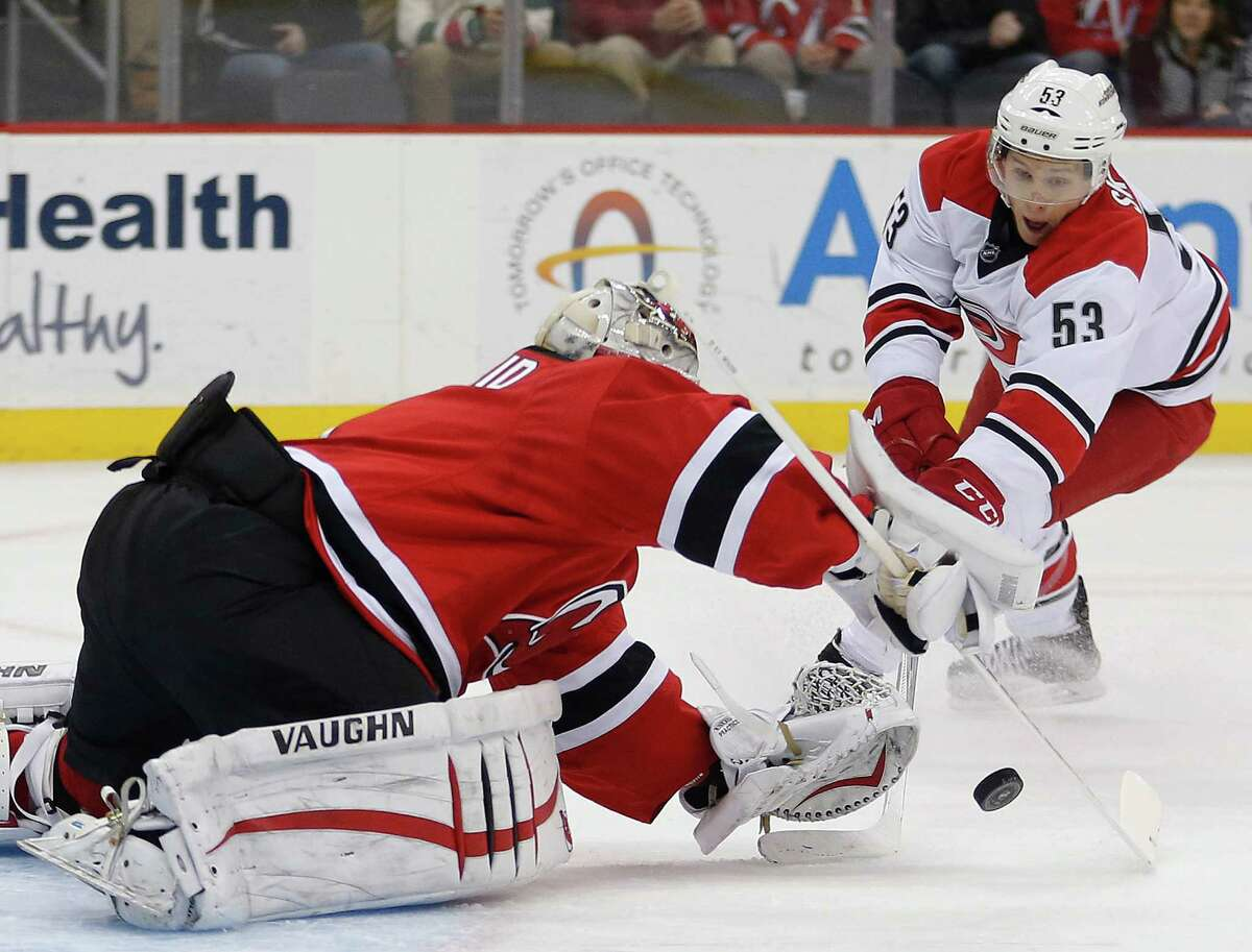 New Jersey Devils goalie Keith Kinkaid, left, makes a save against Carolina Hurricanes left wing Jeff Skinner (53) during the first period of an NHL hockey game Tuesday, Dec. 29, 2015, in Newark, N.J. (AP Photo/Julio Cortez) ORG XMIT: NJJC102
