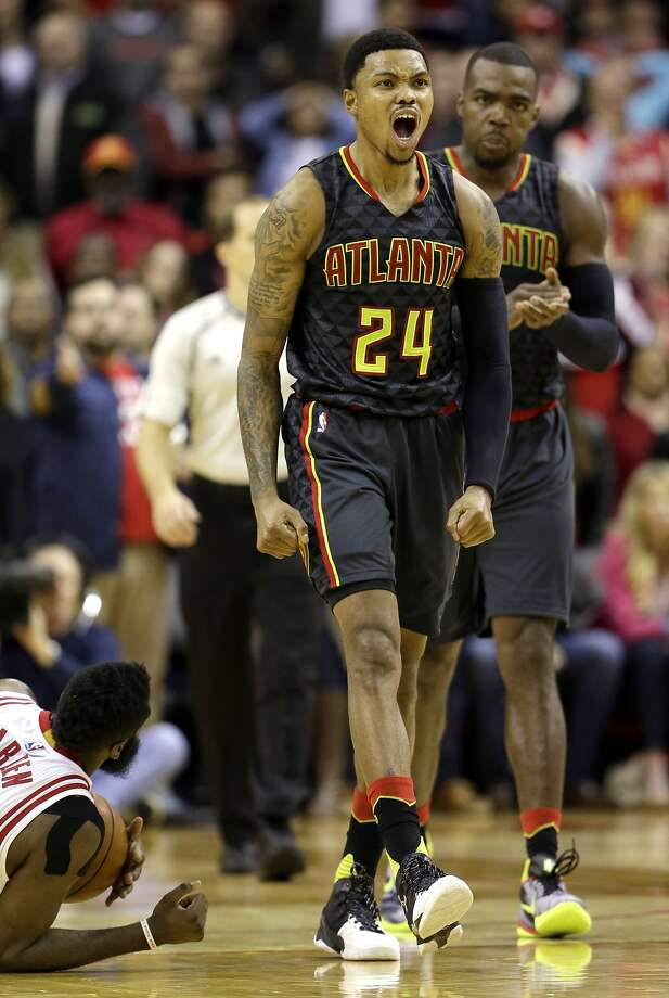 Atlanta's Kent Bazemore emotes after battling Houston's James Harden (lower left) for a loose ball in the second half. Photo: David J. Phillip, Associated Press