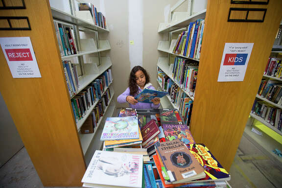 Volunteer Camila Hinojosa, 7, sorts books at Friends of the Houston Public Library, Tuesday, Dec. 29, 2015, in Houston. Volunteers sorted and scanned nearly 1,500 books, which will be donated, sold at events or online, and recycled. Popular book titles will be placed for sale to assist with funding literacy programs and staff scholarships for the Houston Public Library and the books that are selected for donation will be distributed to an array of hospitals, family and children organizations and local charities.