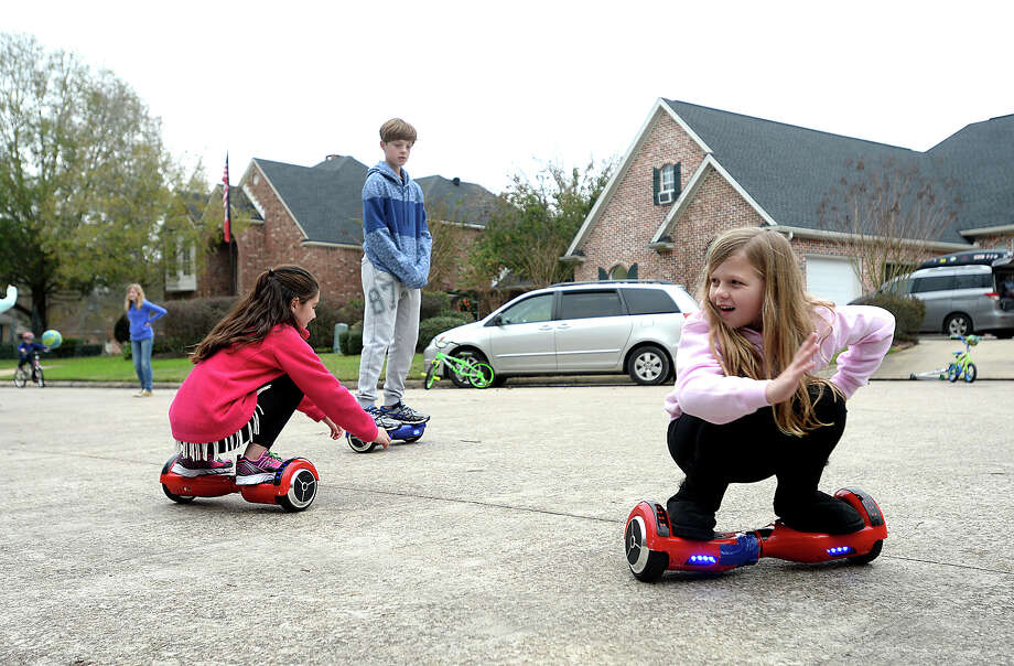 From left, Presley Tyner, 9, Ben Bennett, 12, and Ella Bennett, 9, ride their new hoverboards around their west end neighborhood in Beaumont Tuesday. The new toys were a popular gift this Christmas and have made headlines since as the number of injuries from hoverboard falls have grown over the holiday.  Photo taken Tuesday, December 29, 2015  Kim Brent/The Enterprise Photo: Kim Brent / Beaumont Enterprise