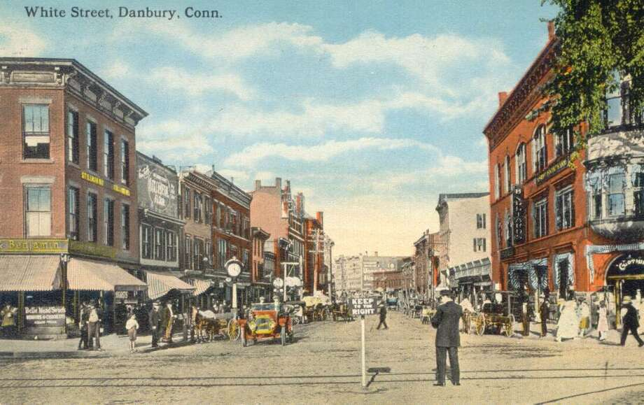 Horses and carriages, horseless carriages and even trolley tracks are visible in this image of White Street, Danbury, on a sunny day. The image is from a postcard mailed in 1917. The postcard is from the collection of Pete Scalzo of Brookfield. Photo: Contributed Photo / The News-Times Contributed