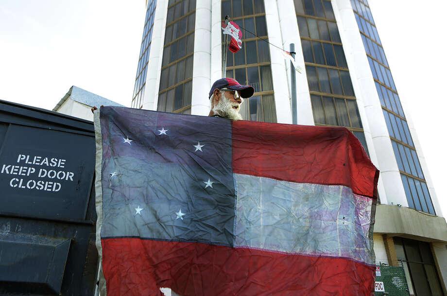 Alfred Stevens, un veterano del Ejercito de los EU, de 55 anos de edad, muestra su bandera confederada despues de buscar comida en varios basureros, frente al Hotel Rio Grande Plaza donde ha estado viviendo a cambio de trabajo que les realiza. Photo: Foto Por Bob Owen, Staff / San Antonio Express-News / San Antonio Express-News