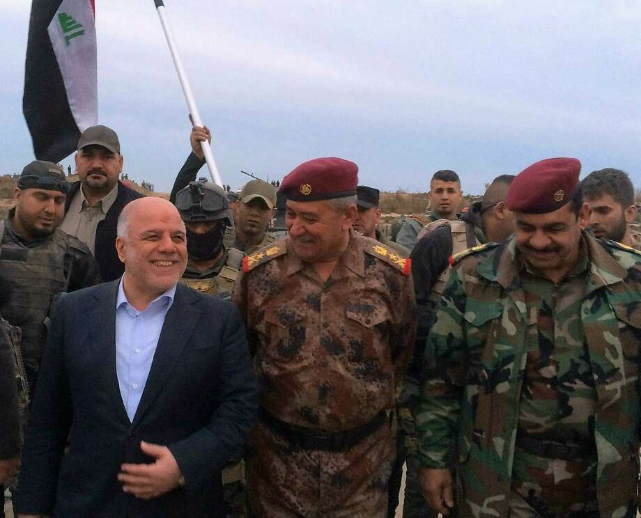 Iraqi Prime Minister Haider al-Abadi walks in liberated Ramadi with Lieutenant-General Abdel Ghani al-Assadi. Photo: -, AFP / Getty Images