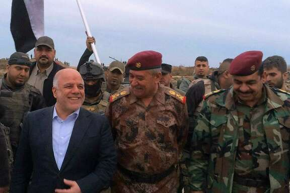 "A handout image released by the press office of Iraqi Prime Minister Haider al-Abadi on it's Facebook page on December 29, 2015, shows him (L) walking with Lieutenant-General Abdel Ghani al-Assadi (C), head of the elite counter-terrorism service that led the battle in the centre of Ramadi, as the city is declared liberated from the Islamic State (IS) group. Abadi congratulated the fighters who retook Ramadi, vowing to liberate the second city of Mosul and rid the entire country of IS in 2016. AFP PHOTO / HO / IRAQI PRIME MINISTER'S OFFICE == RESTRICTED TO EDITORIAL USE - MANDATORY CREDIT ""AFP PHOTO / HO / IRAQI PRIME MINISTER'S OFFICE"" - NO MARKETING NO ADVERTISING CAMPAIGNS - DISTRIBUTED AS A SERVICE TO CLIENTS ==-/AFP/Getty Images"