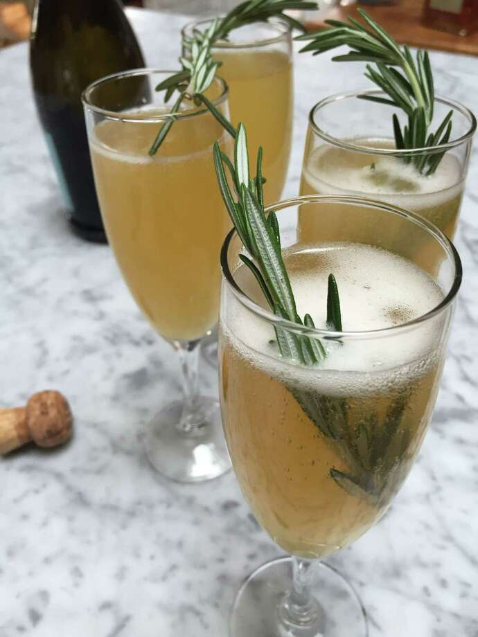 This Dec. 3, 2015, photo, shows sparkling orchard grove cocktails, which spike sparkling wine with an apple cider-orange juice reduction, amaretto liqueur and a sprig of fresh rosemary in Concord, N.H. The New Year's Eve cocktail can be prepared ahead of time. (AP Photo/J.M. Hirsch) Photo: J.M. Hirsch / Associated Press / AP