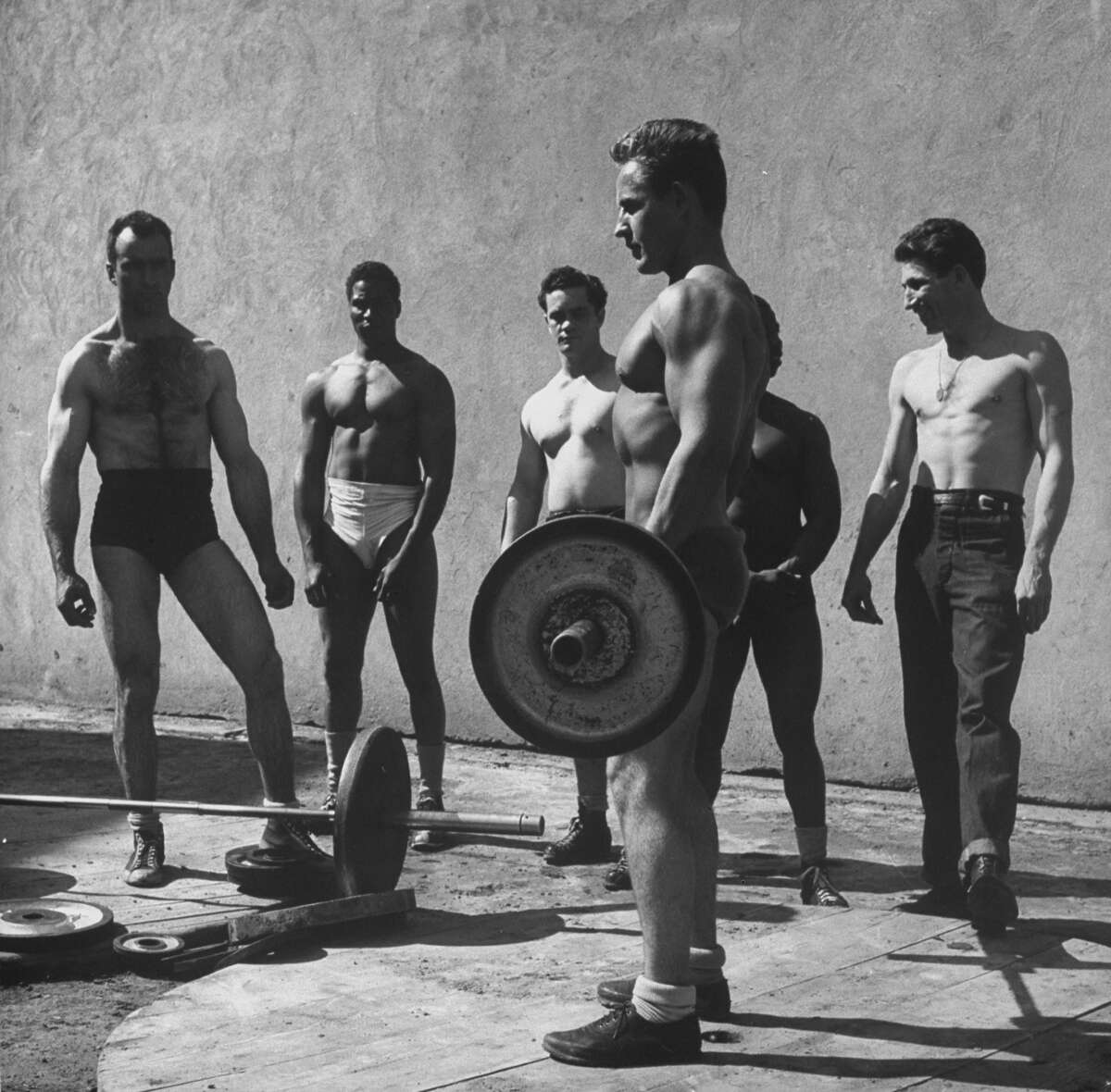Prisoners at San Quentin weightlifting in prison yard during recreation period. San Quentin, California 1947.