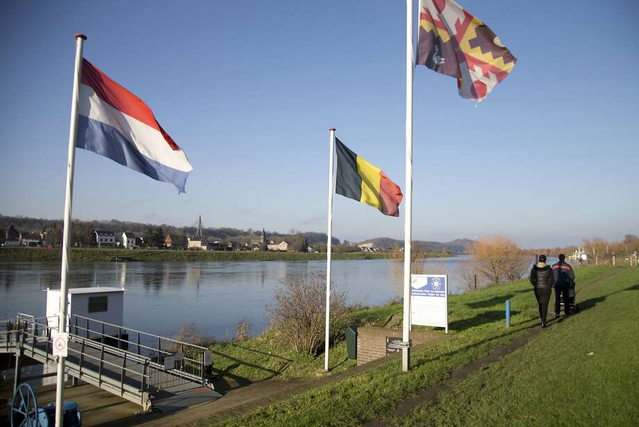 People walk past Dutch and Belgian flags along the Meuse River that divides the two nations. Photo: Virginia Mayo, Associated Press